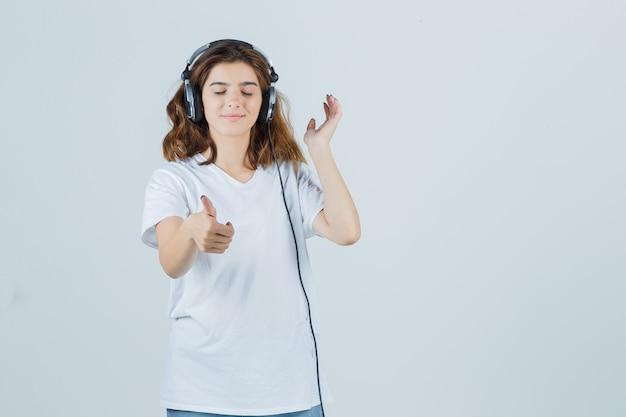 Молодая женщина в белой футболке, джинсах показывает палец вверх, наслаждаясь музыкой в наушниках и выглядит счастливым, вид спереди.