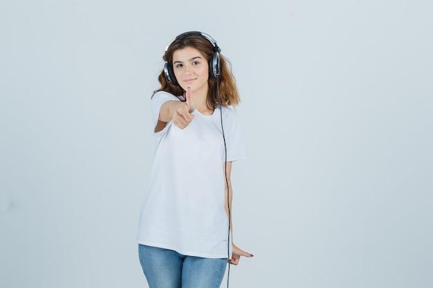 白いtシャツを着た若い女性、ヘッドフォンで音楽を楽しみながら親指を立てて幸せそうに見えるジーンズ、正面図。