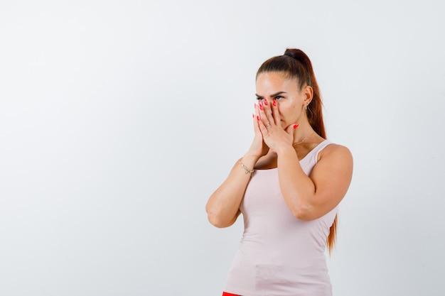Молодая женщина в белой майке, взявшись за руки на носу и глядя задумчиво, вид спереди.