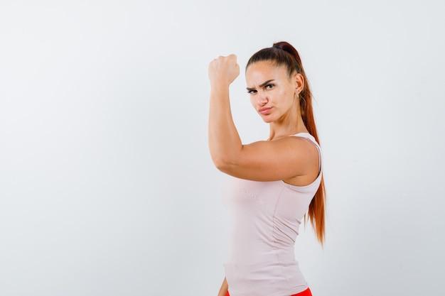 腕の筋肉を示し、自信を持って見える白いタンクトップの若い女性、正面図。