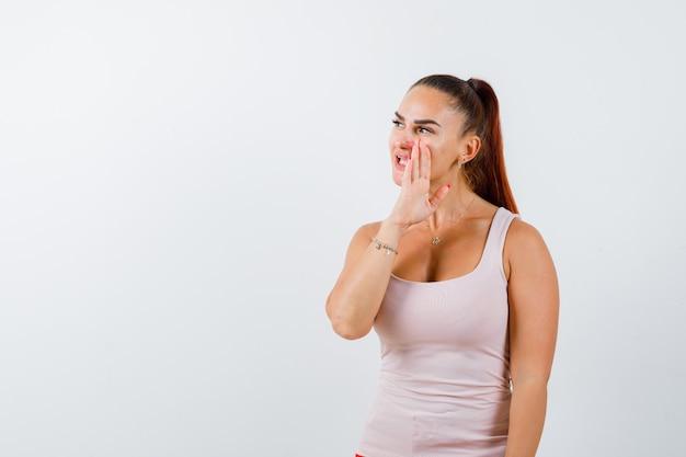 白いタンクトップの若い女性が手の後ろに秘密を告げ、注意深く見ている、正面図。