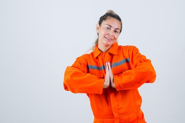 ナマステのジェスチャーを示し、嬉しそうに見える労働者の制服を着た若い女性、正面図。
