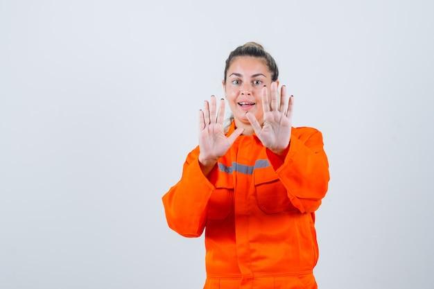 停止ジェスチャーを示し、慎重に見える、正面図の労働者の制服を着た若い女性。