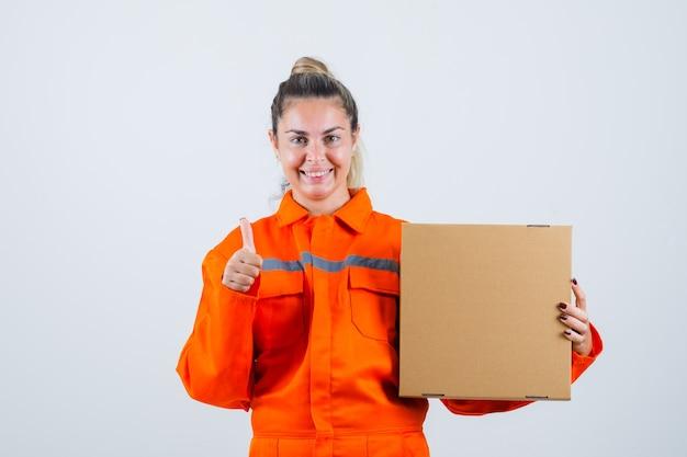 労働者の制服を着た若い女性が箱を持って陽気に見ながら親指を立てて、正面図。