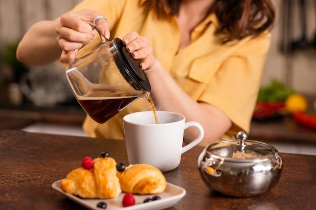 キッチンのテーブルのそばに座って、クロワッサンと一緒に朝食を取りに行く間、カップに紅茶を注ぐ黄色いシャツの若い女性