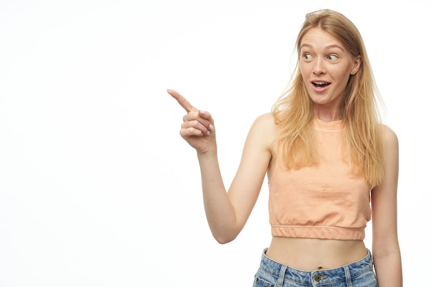 Young female indicates to the copy space with a finger, smiles broadly with happy facial expression on white