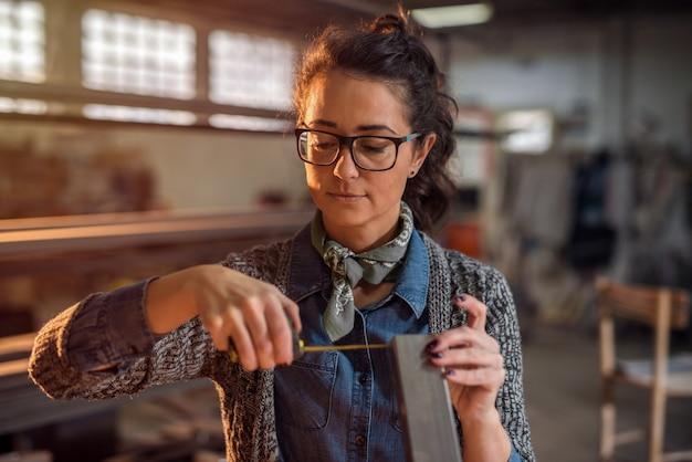 Молодой женский промышленный инженер принимая измерения трубы металла в ее мастерской.