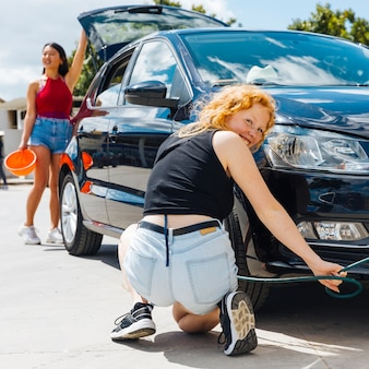 Young female inflating tire of automobile while other woman closing trunk in background