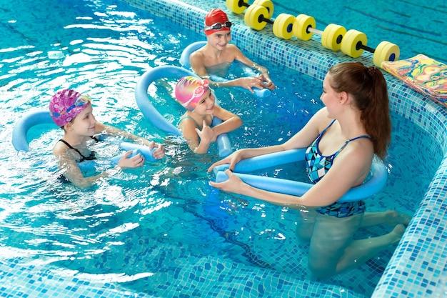 젊은 여성 강사가 아이들에게 수영장에서 수영하는 법을 가르칩니다.