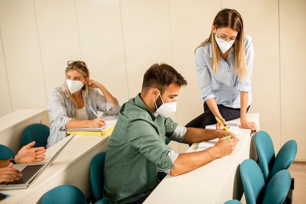 ウイルス対策のための顔面保護医療マスクを着用し、講堂で男子学生を助ける若い女性インストラクター