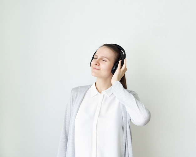 Young female is listening to music with headphones, girl standing in front of light gray wall