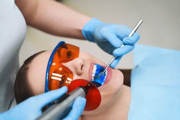 Young female is lying in chair in protective glasses while dentist is giving her root canal