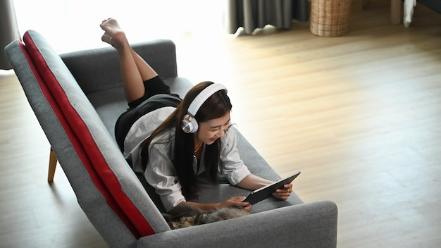 A young female is using tablet during listening to music on a wireless headphone while lying on sofa at home.