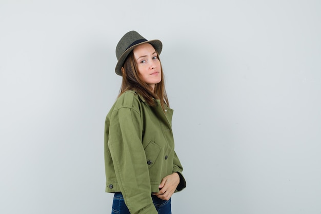 Giovane donna in giacca, pantaloni, cappello e dall'aspetto elegante. .