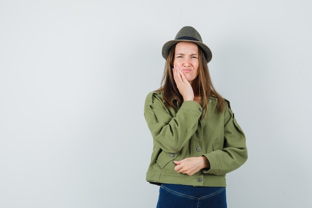 Young female in jacket, pants, hat suffering from toothache and looking uncomfortable , front view.