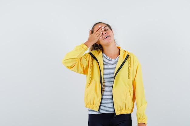 Giovane donna in giacca, t-shirt tenendo la mano sugli occhi e guardando felice, vista frontale.