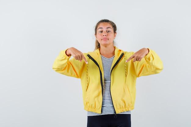 Giovane donna in giacca, t-shirt con la punta rivolta verso il basso e guardando fiducioso, vista frontale.