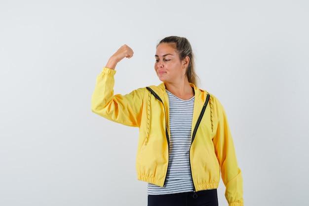 Giovane donna in giacca, t-shirt che mostra il pugno chiuso e guardando fiducioso, vista frontale.