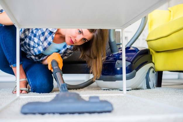 Young female janitor cleaning carpet with vacuum cleaner