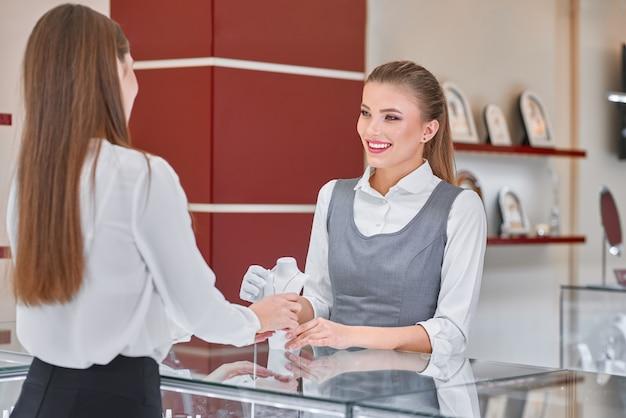 보석 가게에서 여자를위한 목걸이를 선택하는 데 도움이 젊은 여성 보석 노동자