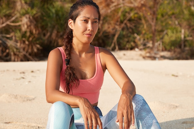 활동적인 마모를 입은 젊은 여성 조깅하는 사람은 건강을 느끼고 신중하게 거리를 보며 모래 사장에서 포즈를 취합니다.