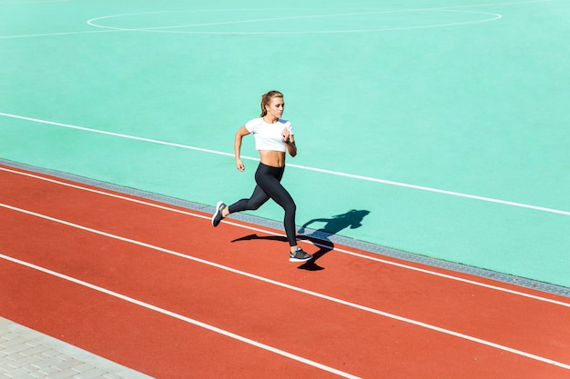 Young female jogger running at stadium