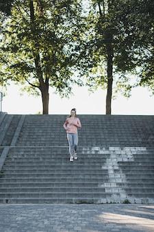若い女性のジョガーが都市公園の階段を駆け下ります