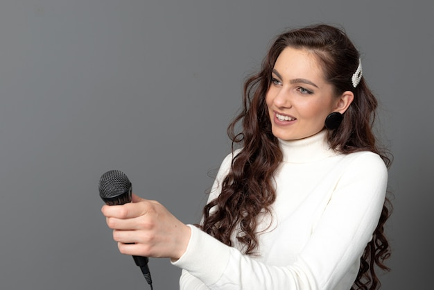 Young female journalist is standing and stretching a microphone forward, isolated on gray