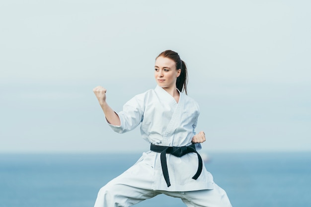 Young female karate athlete preparing to attack. she is wearing black belt and white kimono