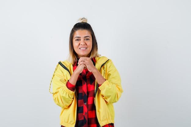 市松模様のシャツ、ジャケットで顔の近くに握りしめられた手を保ち、至福の正面図を探している若い女性。