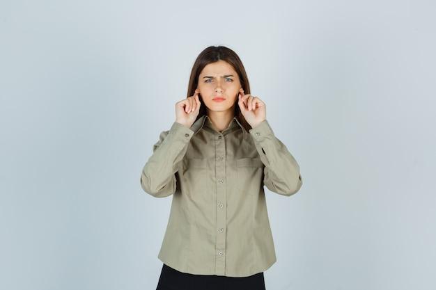 셔츠, 치마에 귀 뒤에 손가락을 유지하고 우울한 찾고 젊은 여성. 전면보기.