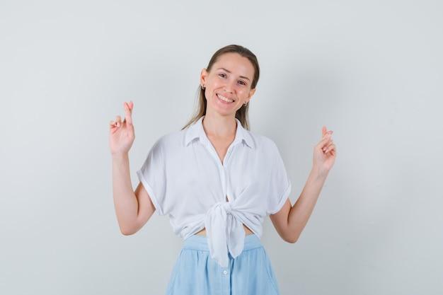 Giovane femmina mantenendo le dita incrociate in camicetta e gonna e guardando felice