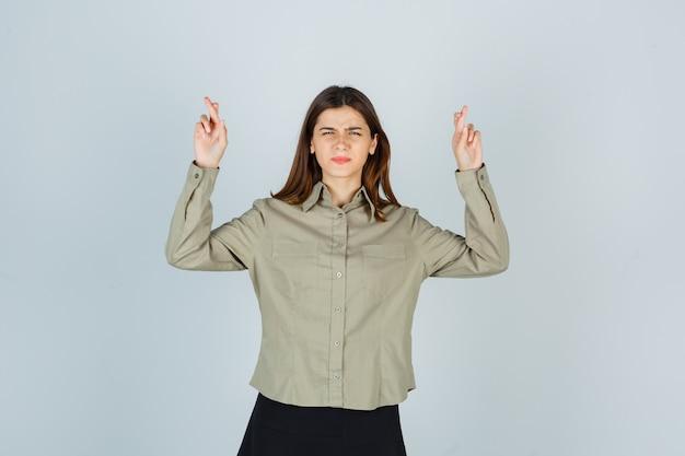 Giovane femmina tenendo le dita incrociate mentre aggrotta le sopracciglia in camicia, gonna e sembra confusa