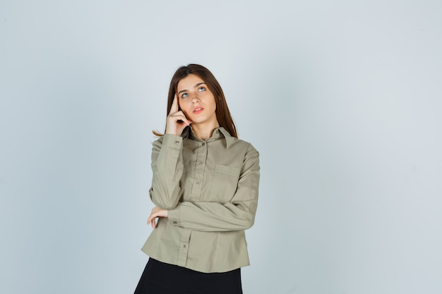 Giovane donna che tiene le dita sulle tempie, alza lo sguardo in camicia, gonna e sembra pensierosa. vista frontale.