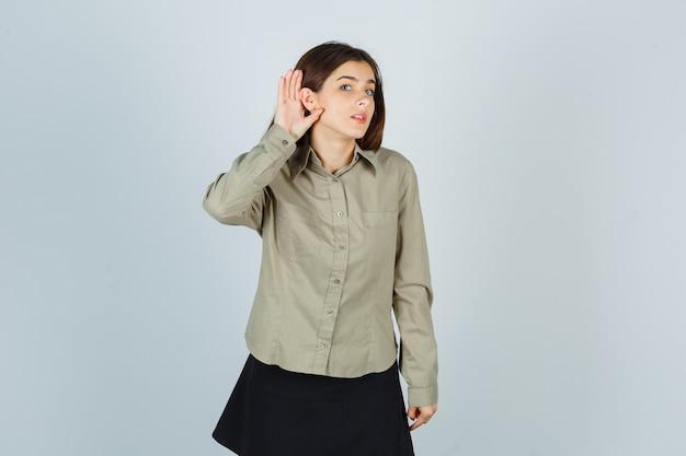 Молодая женщина держит руку за ухом в рубашке, юбке и выглядит любопытно