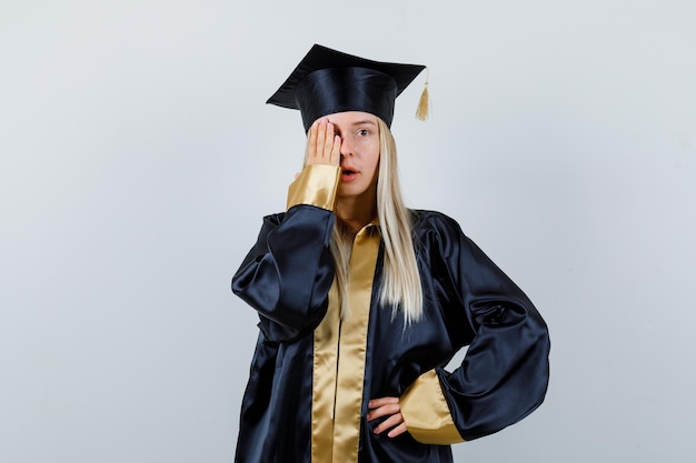 Giovane donna che tiene la mano sull'occhio in uniforme laureata e sembra concentrata.