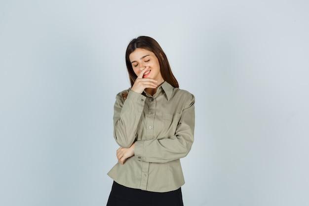 Молодая женщина держит руку на подбородке, закрывая глаза в рубашке, юбке и выглядит веселой, вид спереди.