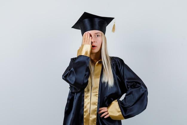 Молодая женщина держит руку на глазу в униформе выпускника и выглядит сосредоточенной.