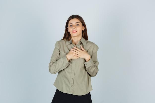 Giovane donna che tiene le mani sul petto in camicia, gonna e sembra grata. vista frontale.