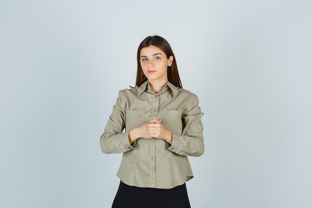 Young female keeping hands over chest in shirt, skirt and looking sensible