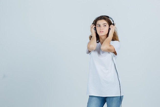 Young female keeping hands on her headphones in white t-shirt, jeans and looking dreamy , front view.