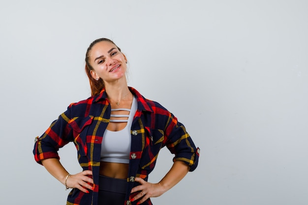 Young female keeping hands on hip in crop top, checkered shirt, pants and looking happy , front view.