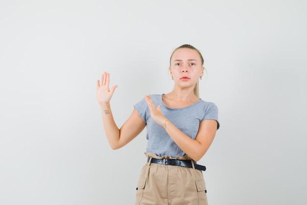 T- 셔츠, 바지에 예방적인 방식으로 손을 유지하고 불안해 보이는 젊은 여성. 전면보기.
