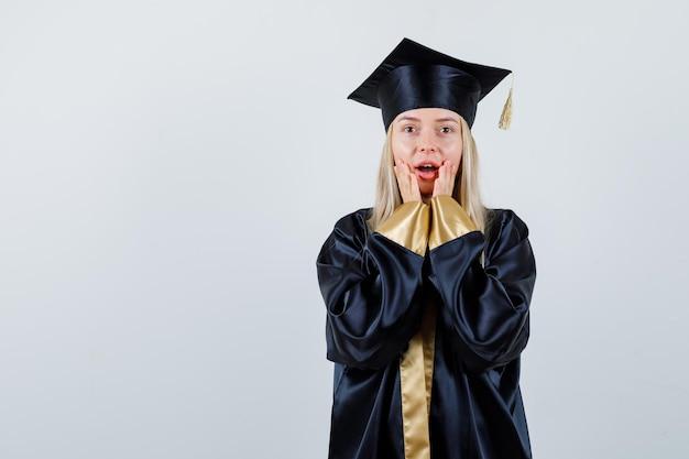 若い女性は、卒業生の制服を着て開いた口の近くで手を保ち、驚いているように見えます。