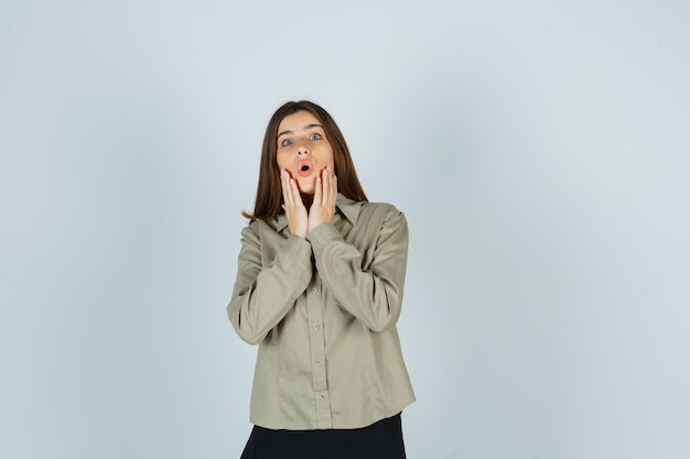 Giovane donna che tiene le mani vicino alla bocca aperta in camicia, gonna e sembra meravigliata. vista frontale.