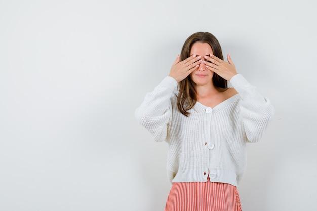 カーディガンとスカートの目を落ち着いて孤立して見える若い女性