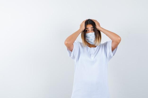 T- 셔츠, 마스크에 머리에 손을 유지 하 고 건망증을 찾는 젊은 여성. 전면보기.