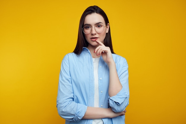 Young female keeps finger near lips wears glasses and blue shirt
