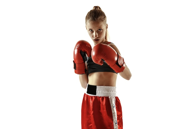Young female kickboxing fighter posing confident on white wall. caucasian blonde girl in red sportswear practicing in martial arts. concept of sport, healthy lifestyle, motion, action, youth.
