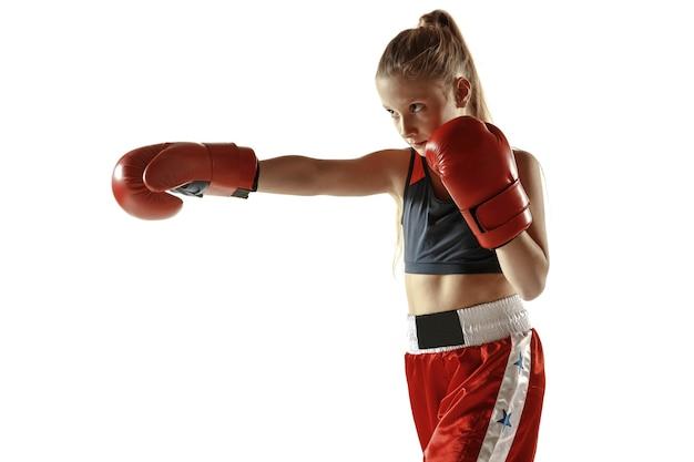 白い壁に隔離された若い女性のキックボクシングの戦闘機のトレーニング。武道の練習をしている赤いスポーツウェアの白人のブロンドの女の子。スポーツ、健康的なライフスタイル、運動、行動、若者の概念。